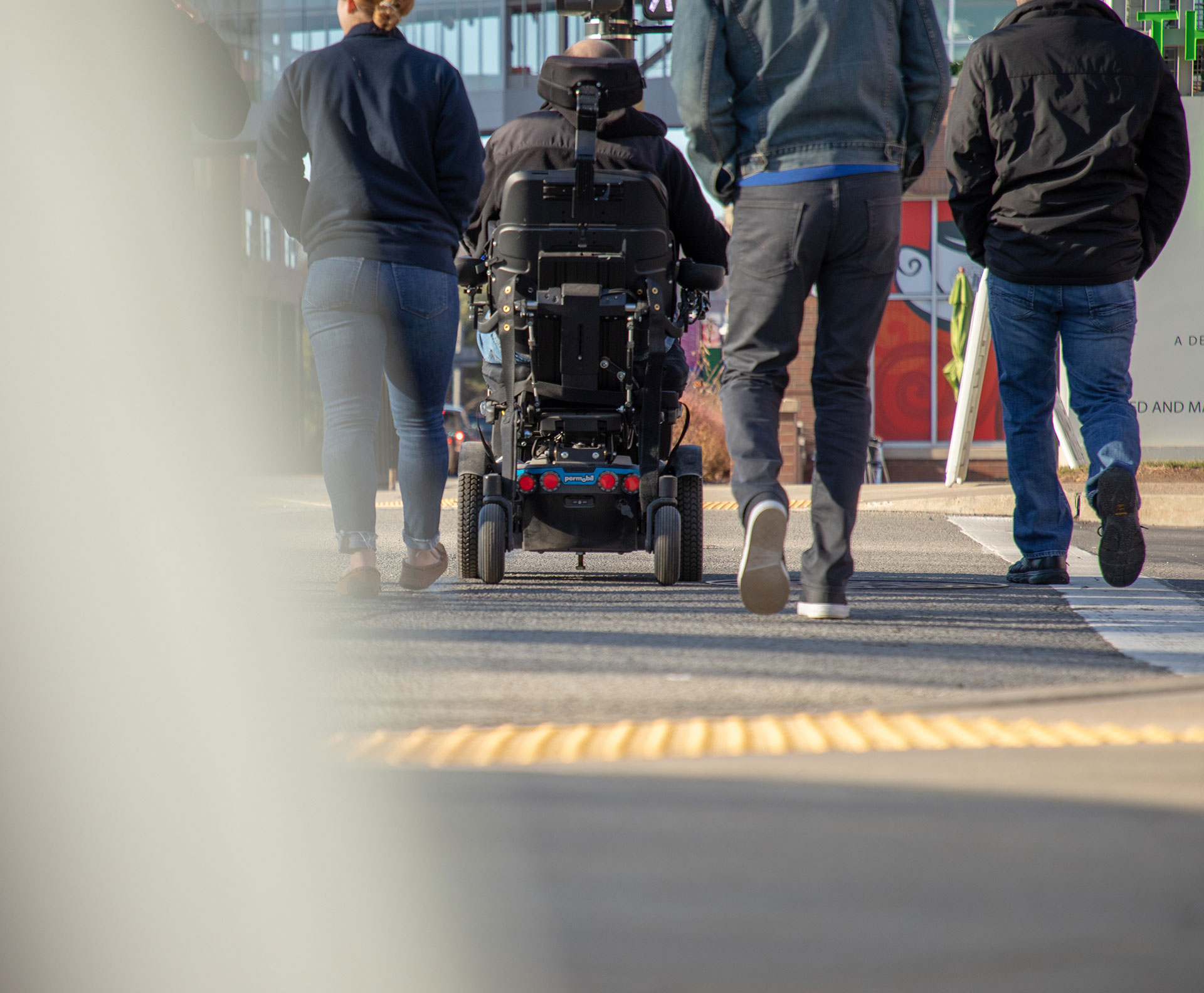 a group of pedestrians crossing the street together, one man uses a power wheelchair